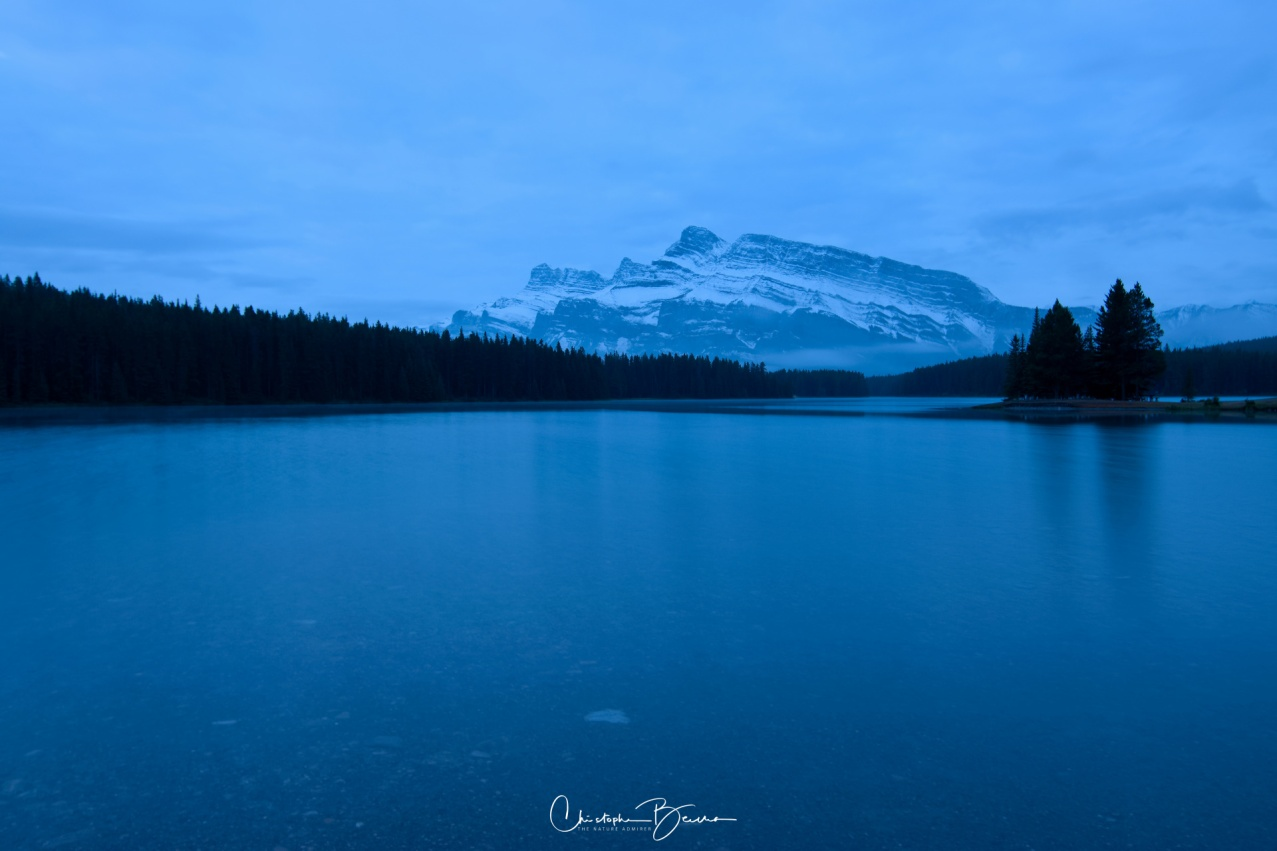 Blue hour at Two Jack Lake. The long exposure smooths out the water, with Mount Rundle's more jagged face on the background.