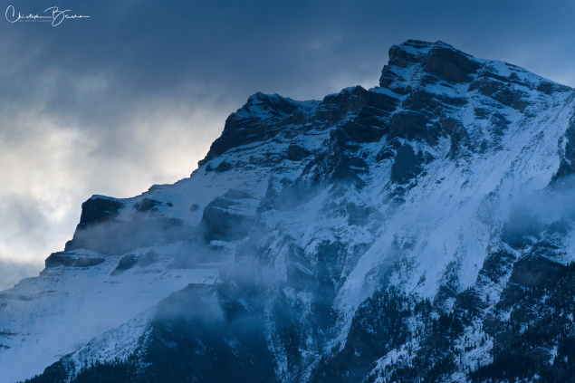 Close up of one summit, with clouds illuminated by the sun on the back.